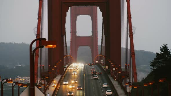 Cover Image for Slow Motion Shot of Evening Car Traffic Lights Moving Along Iconic Golden Gate Bridge in Late Sunset
