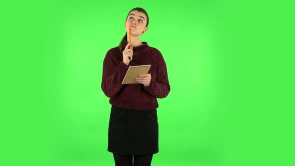 Cover Image for Girl Stands and Thinks, Then Writes with Pencil in Notebook. Green Screen