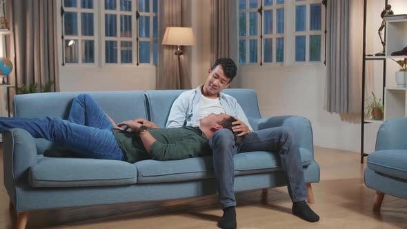 Young Asian Gay Couple Spend Time At Home. Two Happy Man In Love Lie Down On Sofa. Lgbt Relationship