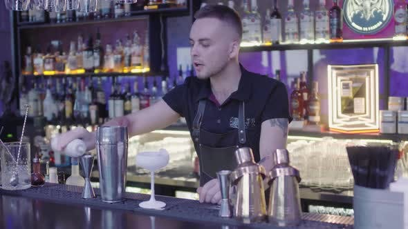 Cover Image for Cute Professional Barman Pouring Drink From Measuring Cup Into a Metal Shaker