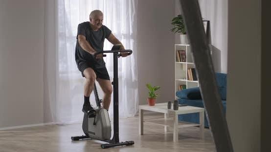 Gesunder Lebensstil und Fit im mittleren Alter trainiert mit stationärem Fahrrad zu Hause