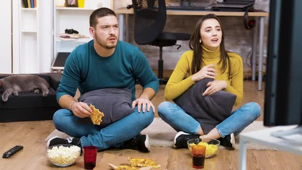 Thumbnail for Disappointed Couple Sitting on the Floor While Watching Sport
