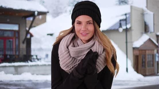 Thumbnail for Portrait of millennial girl in winter wear, standing in snowy street in town