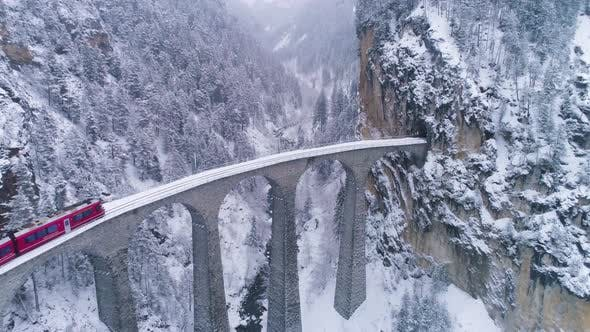 Landwasser Viaduct with Railway and Train at Winter Day. Snowing. Switzerland. Aerial View