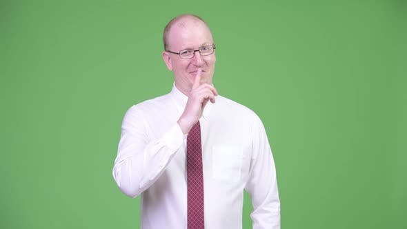 Thumbnail for Happy Mature Bald Businessman with Finger on Lips