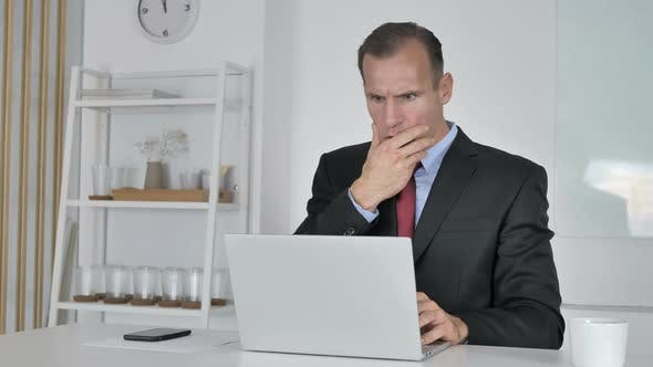 Shocked Middle Aged Businessman Working on Laptop, Astonished