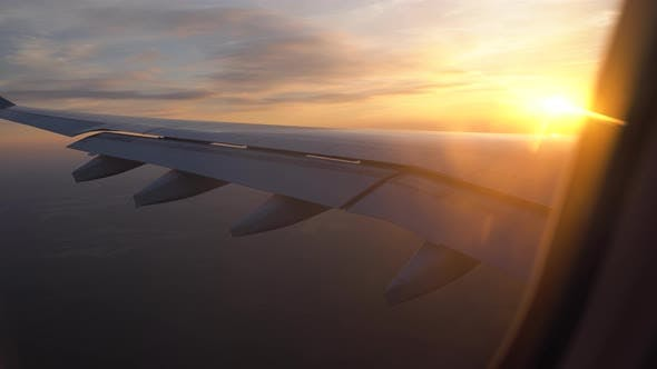 Thumbnail for Sunset in the Window of the Plane. Beautiful View of the Aircraft Wing. Passenger Transportation and