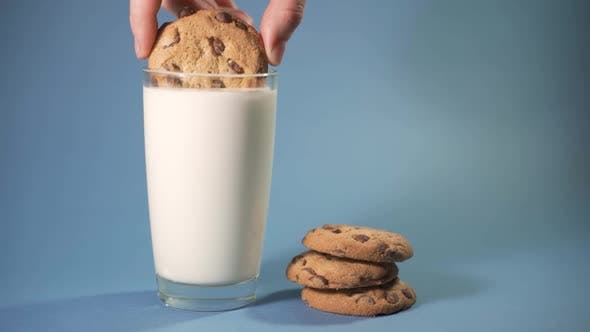 Thumbnail for Hand Dipping a Cookie Into Glass of Milk