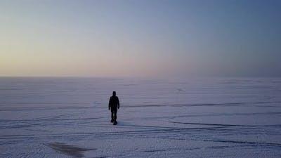 Drone View Man Walking on Icy Lake