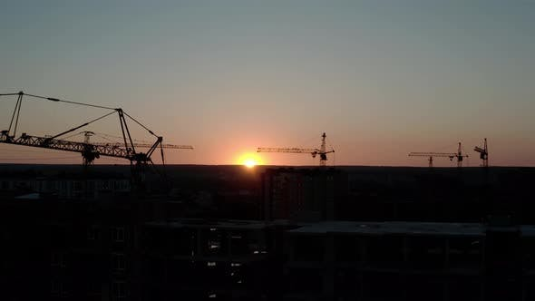Thumbnail for Aerial Drone View of silhouetteConstruction Cranes in Sunset Light. Construction Site Building in