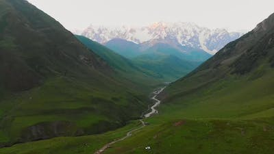 Scenic Zoom Out View Of Ushguli Valley Pass And Shkhara Peak In Background