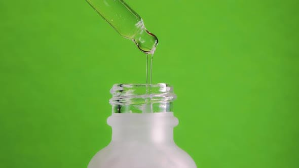 Collagen Essence Dripping From Pipette Into Frosted Glass Jar