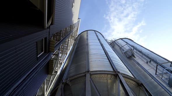 Thumbnail for Modern granary under blue sky. Large aluminum containers for storing grains.