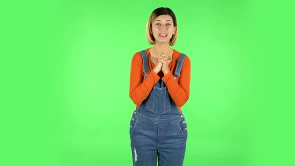 Thumbnail for Girl Looks with Tenderness with Folded Arms in Front of Her. Green Screen