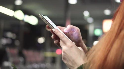 Nahaufnahme der weiblichen Hände mit Smartphone in Night City