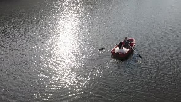 Thumbnail for Aerial Shot of Brides Swim in a Red Boat. The Bright Sun Is Reflected in the Lake Creating a