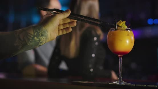 Thumbnail for Close-up of Male Caucasian Hand with Tattoo Preparing Cocktails in Night Club. Visitors Standing