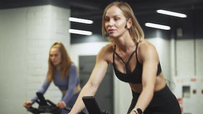 Wellness Females Training on a Spin Bikes Two Women Performs Aerobic Endurance Training on the