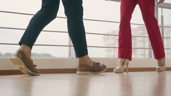 Legs of a Man and a Woman Approaching Each Other Indoors. Man and Woman Go To Meet Each Other.