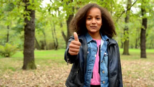 Thumbnail for Young African Happy Girl with Fluffy Afro Shows Thumb Up in the Park - Eye Contact - Agree