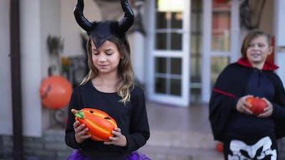 Charming Girl in Demon Devil Costume Posing with Jack O'lantern Greeting Boy in Vampire Costume