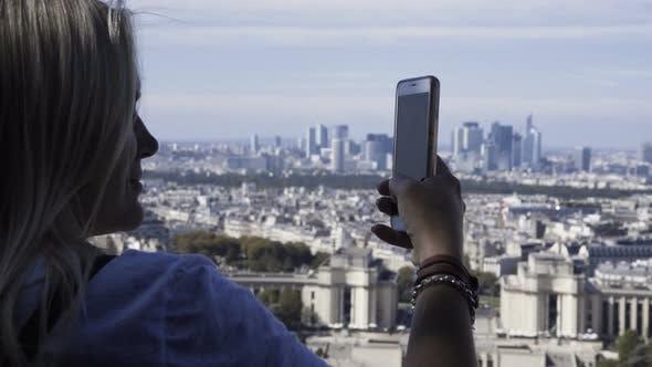 Woman Taking Photo of Cityscape