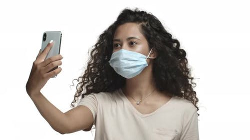 Closeup of Beautiful Latino Woman with Curly Long Hair Wearing Medical Mask During Coronavirus