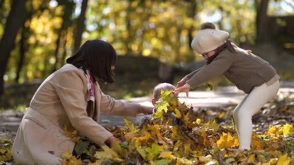 Thumbnail for Happy Mom with Special Girl Throwing Leaves on Boy