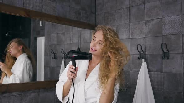 Thumbnail for Blonde Woman Looking at Her Reflection in the Mirror and Smiling while Drying Her Long Curly Hair