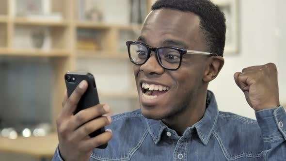 Thumbnail for Excited Happy Afro-American Man Using Smartphone