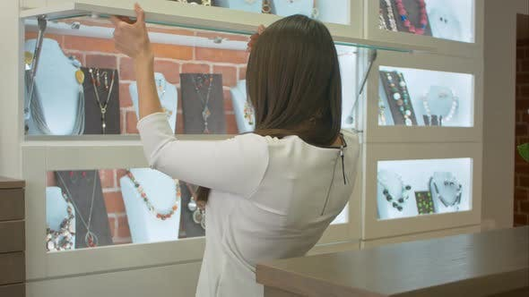Thumbnail for Young Attractive Shopassistant Looking on the Showcase in Jewelry Shop