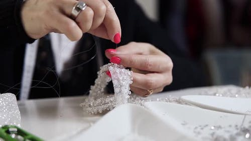 Closeup of Female Hands with Pink Manicure Holding Needle and Thread and Decorating Exclusive