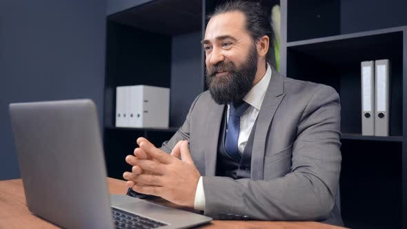 Portrait Middle Aged Businessman Using Webcam for Call in Office
