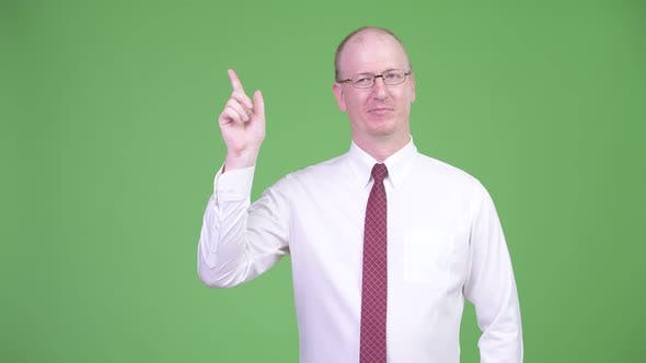 Thumbnail for Happy Mature Bald Businessman Thinking While Pointing Up