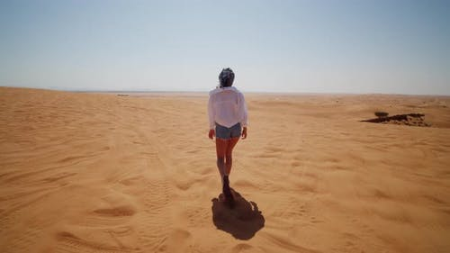 Following a Young Woman Walking in the Desert
