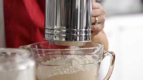 Closeup of woman sifting flour in kitchen