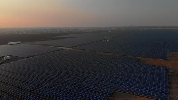 Thumbnail for Aerial Drone View Into Large Solar Panels at a Solar Farm at Bright Sunset. Solar Cell Power Plants