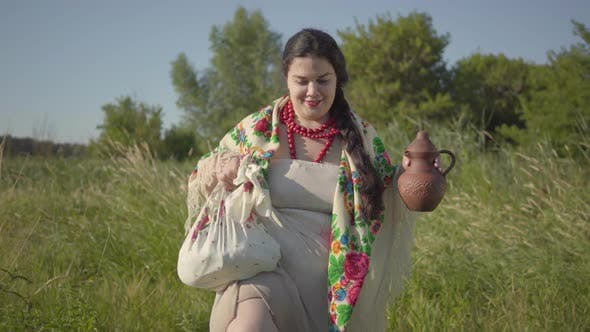 Thumbnail for Beautiful Overweight Woman Walking in Wild High Grass with the Earthen Jar in the Green Summer Field