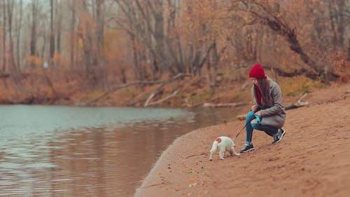 Mädchen sitzt mit einem kleinen Hund nahe der Küste und behandelt den Welpen mit einem Leckerbissen. Spazieren Sie am Fluß im