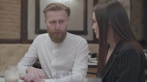 Thumbnail for Glamour Brunette Woman and a Bearded Blond Man Sitting at the Table