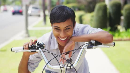 Thumbnail for Black woman ringing bicycle bell and smiling outdoors