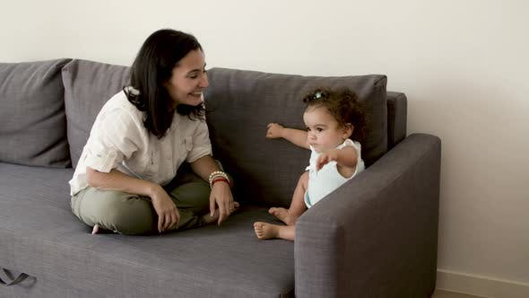 Happy Mom Sitting on Sofa Trying to Make Serious Kid Laugh