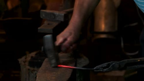Blacksmith Forges Hot Iron in the Forge