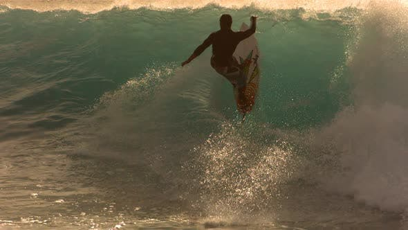 Thumbnail for Surfer rides wave in late afternoon light, slow motion