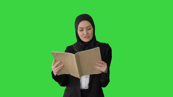Thumbnail for Surprised Muslim Businesswoman Reading Business Diary and Shaking Her Head While Walking on a Green