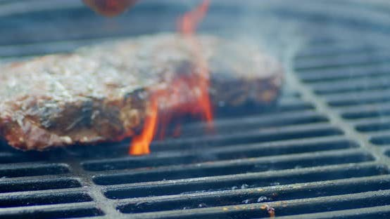 Striploin Steaks Are Turned Over on an Open Fire on the Grill