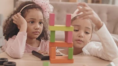 Girls Building Tower with Wooden Bricks