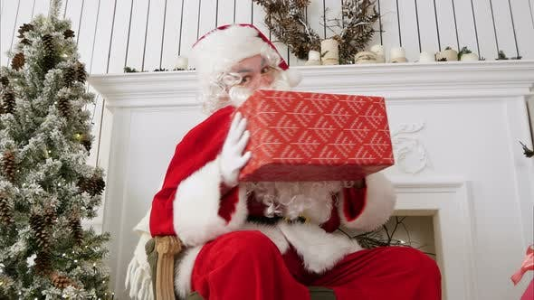 Thumbnail for Santa Claus Looking at the Camera and Teasing with a Present