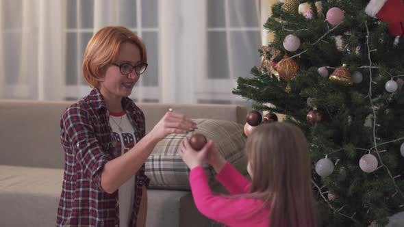 Thumbnail for Funny Little Girl Helping Her Mother Decorating the Christmas Tree