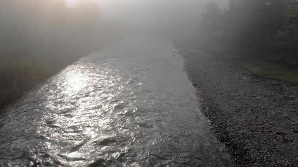River Flowing Through Mountain Village in a Foggy Morning